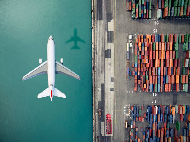 airplane flying over container port - logistica foto e immagini stock
