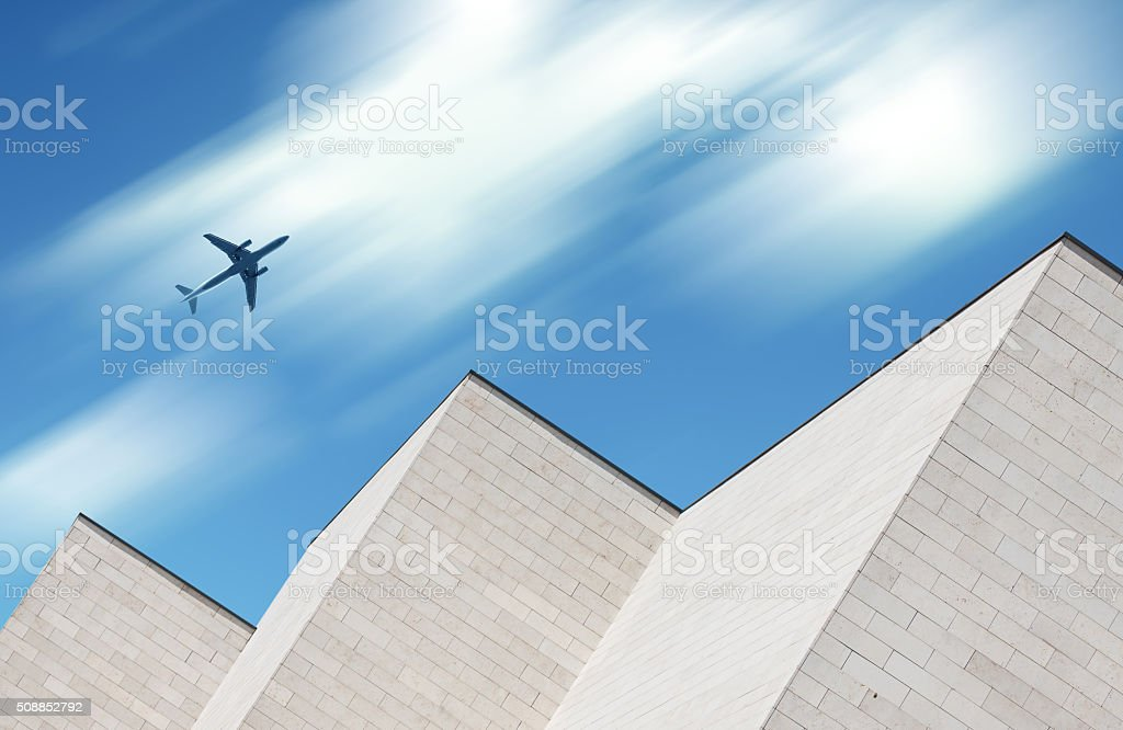 Airplane flying over modern building stock photo
