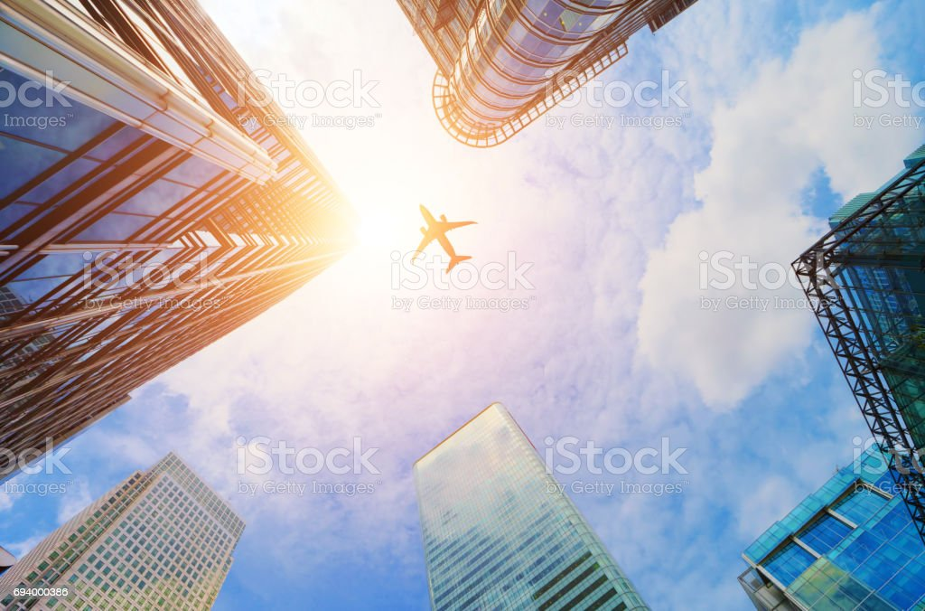 Airplane flying over modern business skyscrapers. Transport, travel. stock photo