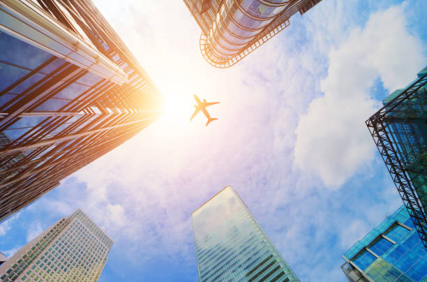 airplane flying over modern business skyscrapers. transport, travel. - business travel stock photos and pictures