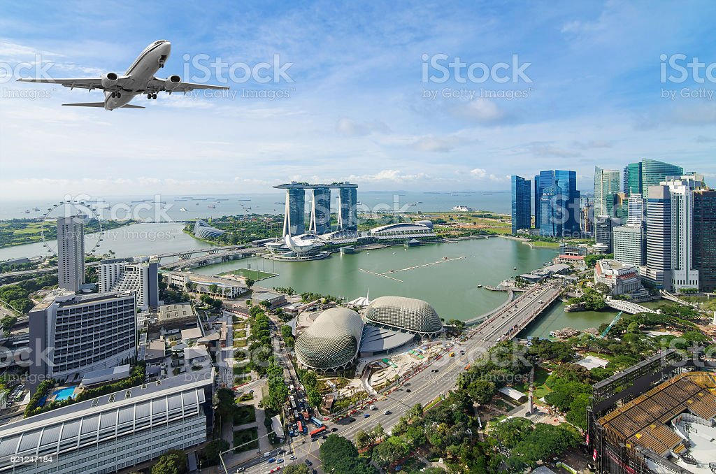 Airplane flying over Singapore stock photo