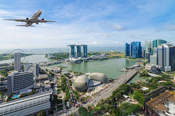 airplane flying over singapore - singapur fotografías e imágenes de stock
