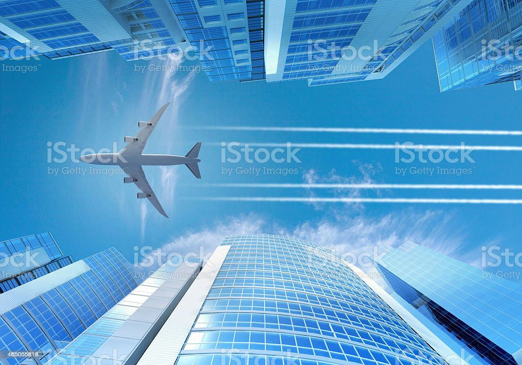 Airplane flying over skyscrapers in city dowtown with blue sky stock photo