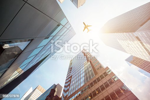 182061540 istock photo Airplane Flying Over Skyscrapers in New York 958707976