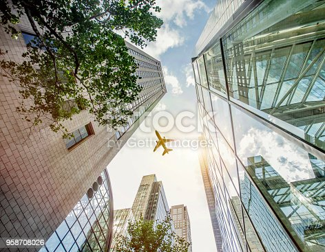 182061540 istock photo Airplane Flying Over Skyscrapers in New York 958708026