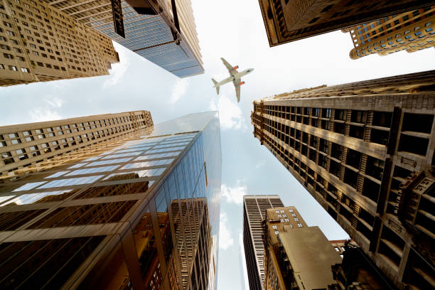 Airplane flying over skyscrapers, Lower Manhattan, NYC.