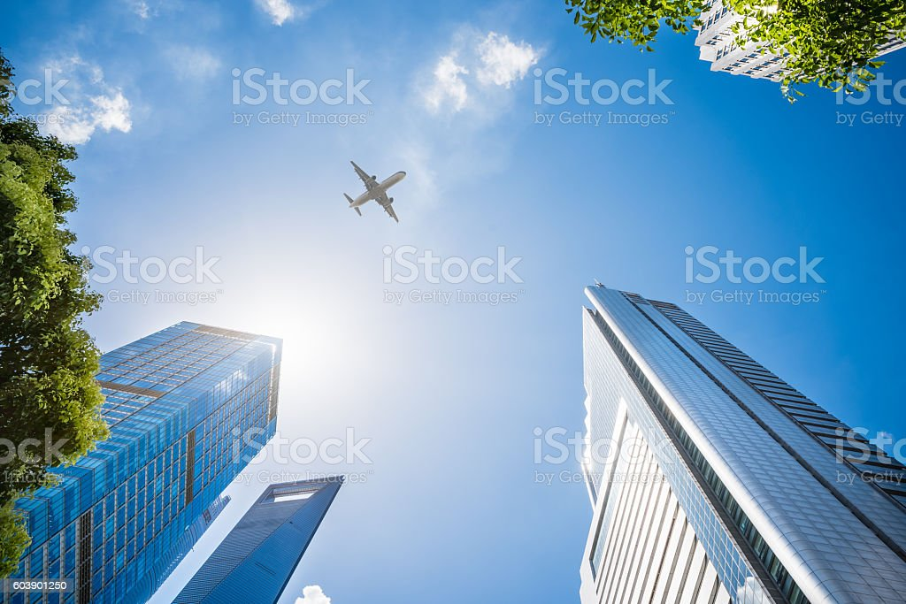 Airplane Flying Over Skyscrapers stock photo