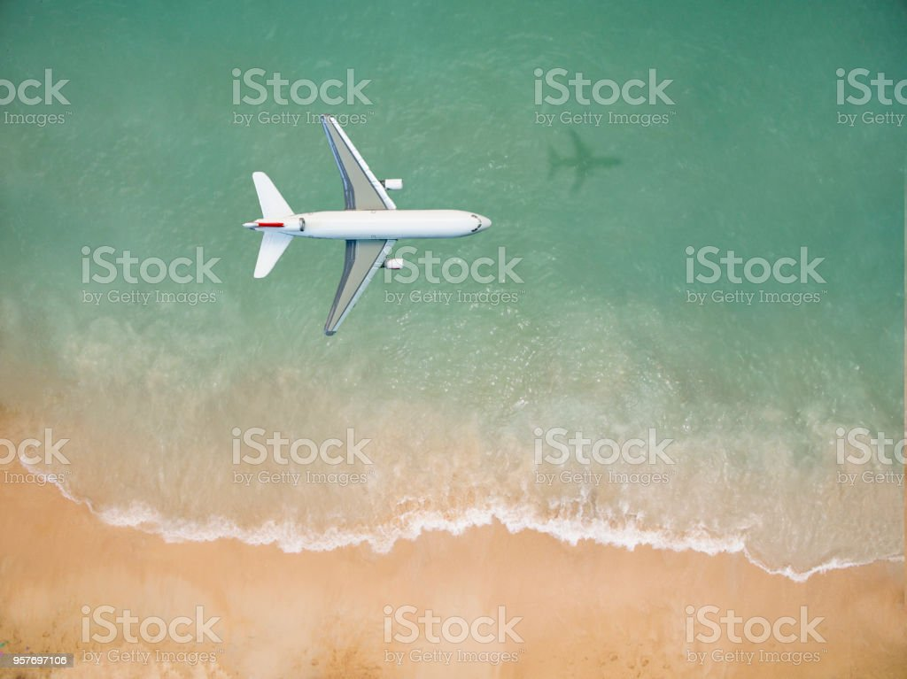 Airplane flying over the beach stock photo