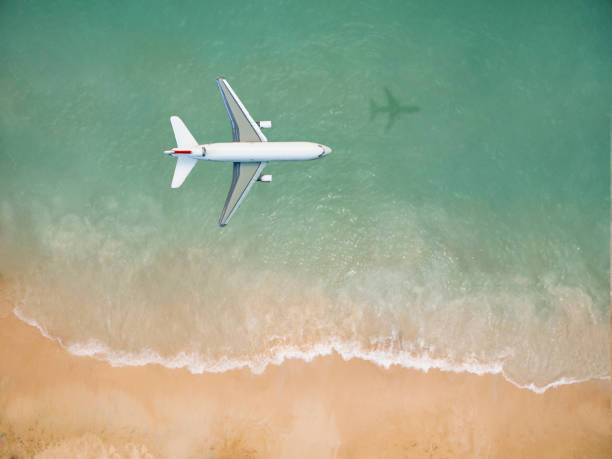 airplane flying over the beach - aereo di linea foto e immagini stock