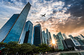 Airplane flying over the financial district in Singapdre City at sunset
