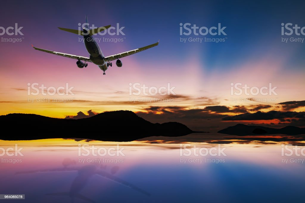 Airplane flying over tropical sea at beautiful light sunset or sunrise with reflex in the water at phuket thailand scenery background. - Royalty-free Air Vehicle Stock Photo