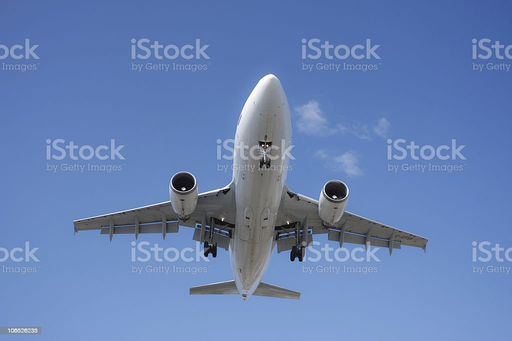 Airplane flying overhead stock photo