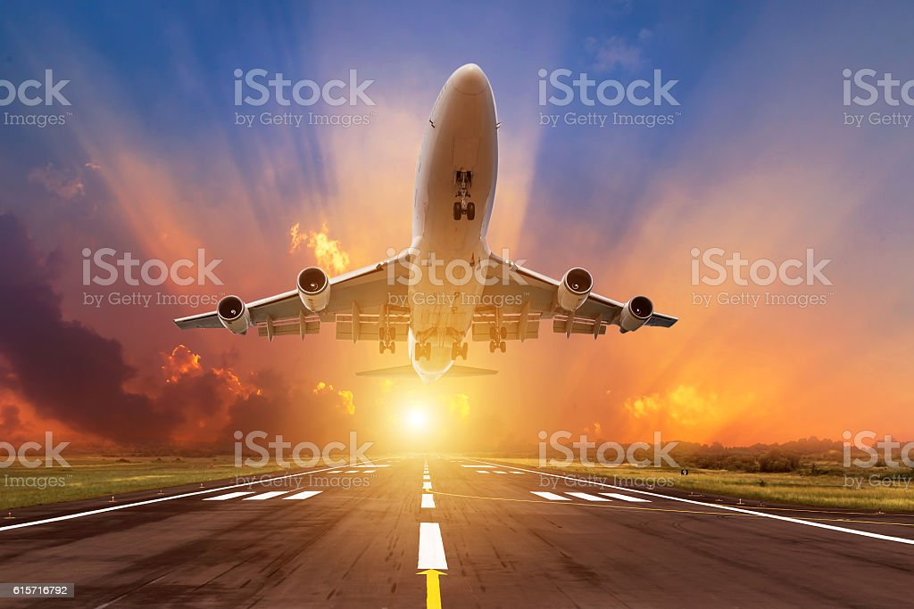 airplane flying take off from runway with sunset stock photo