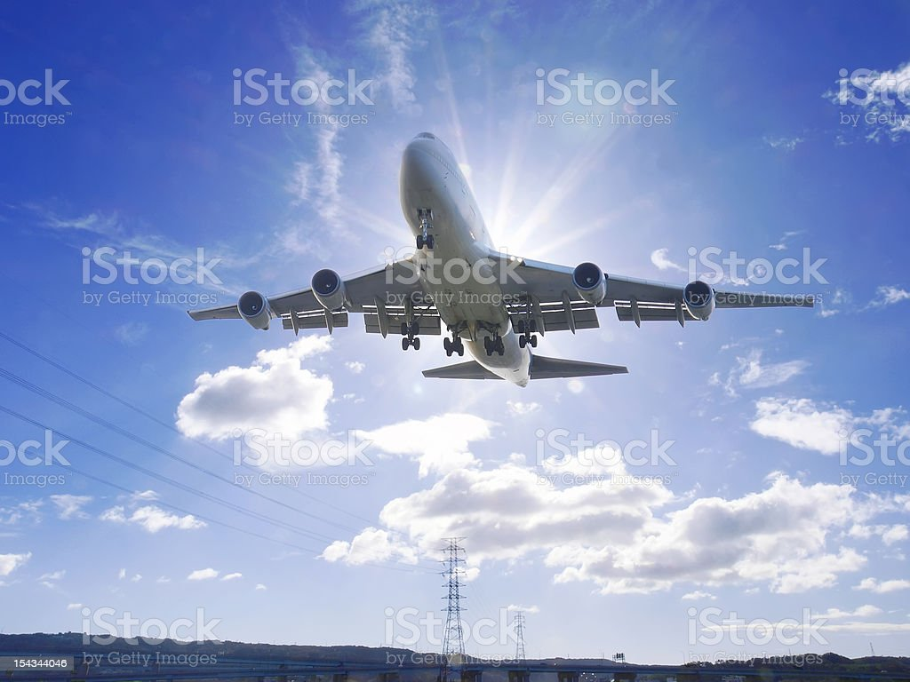 Airplane flying under sunlight stock photo