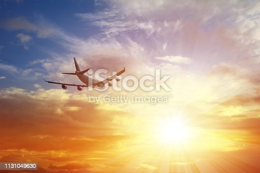 Airplane flying under sunset.
