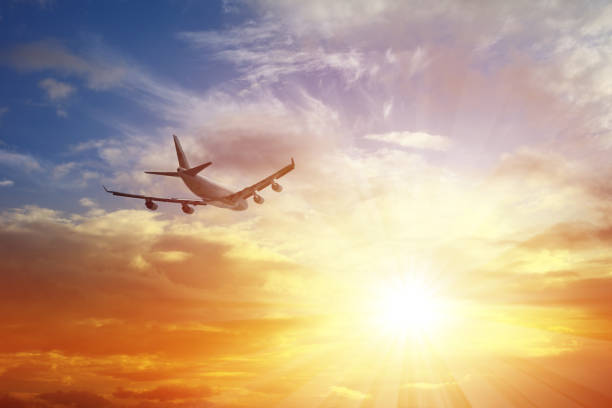 Airplane Flying Under Sunset stock photo