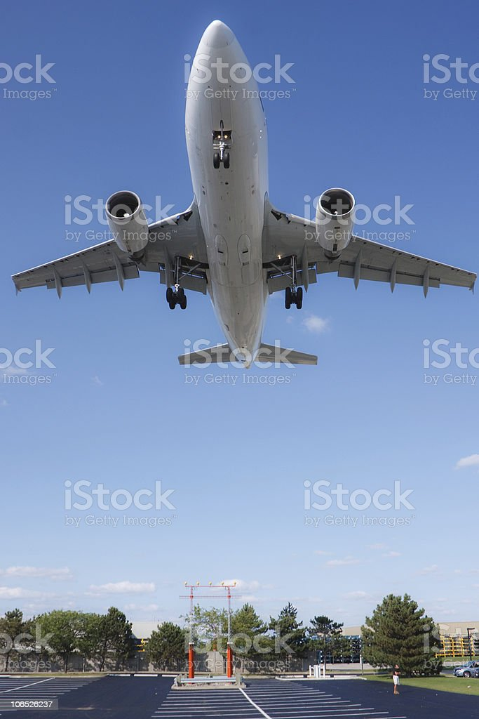 Airplane flying very close to the ground stock photo