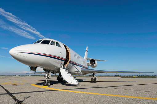 Low angle view of luxury airplane for private flights stationary on airport runway against blue sky. Private jet is ready to boarding with open vehicle door - boarding stairs. No people shot, front view composition and space for copy.
