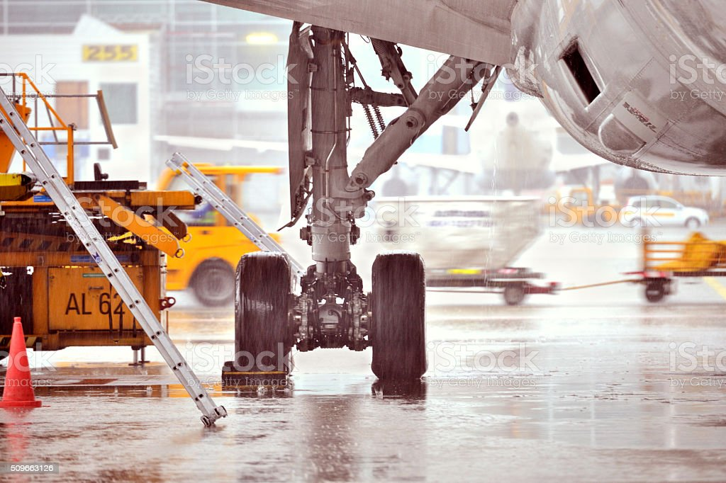 Airplane getting being service in heavy rain stock photo