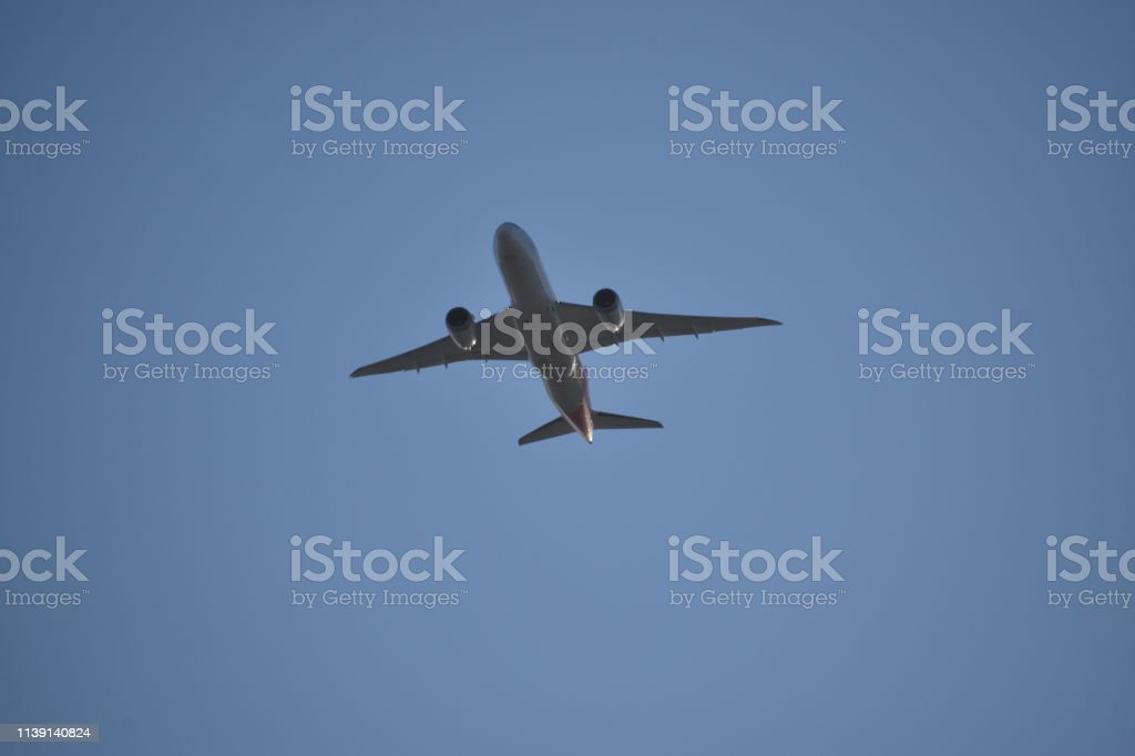 Airplane in Clear Blue Sky stock photo