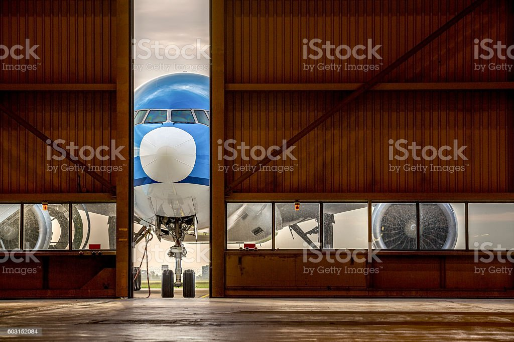 Airplane in front of half opened door to hangar stock photo