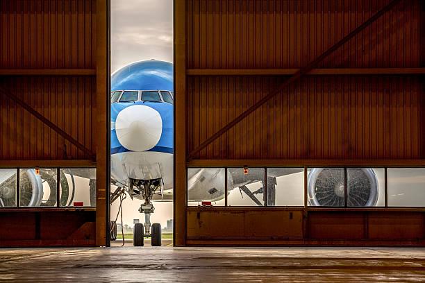 Airplane in front of half opened door to hangar stock photo
