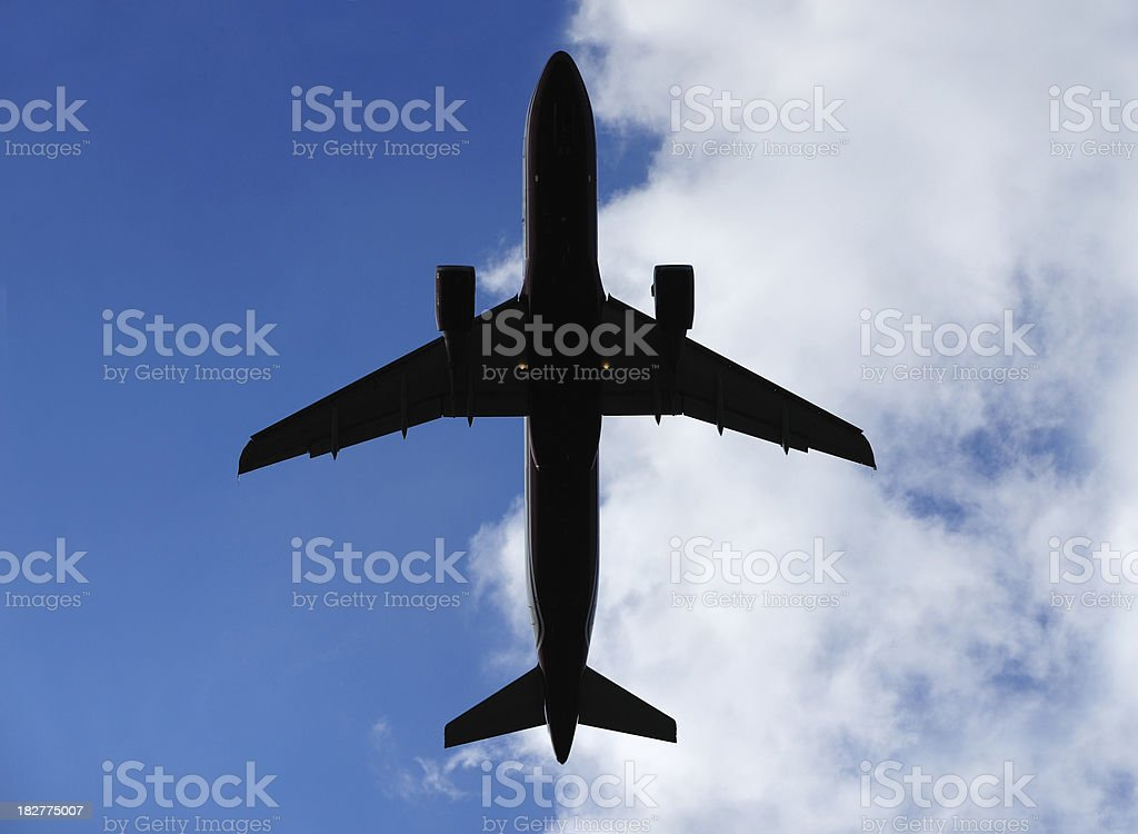 Airplane in silhouette against half blue sky royalty-free stock photo