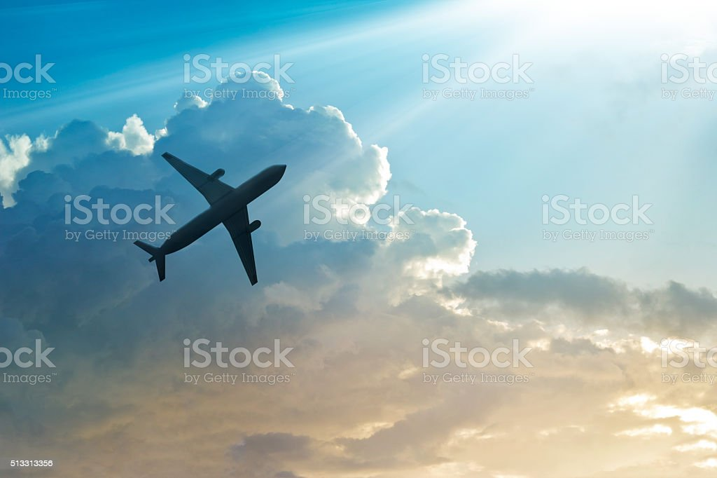 Airplane in the sky and cloud at sunrise stock photo
