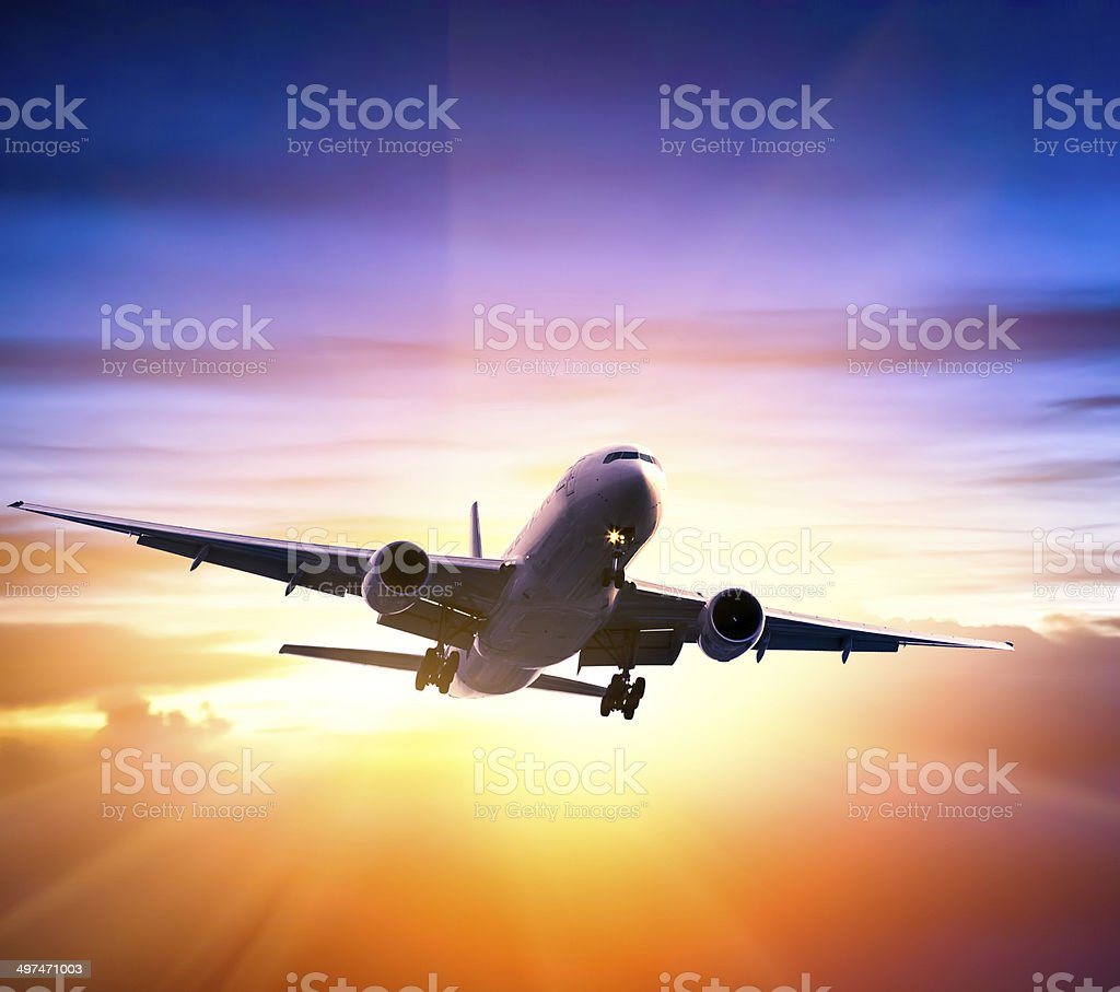 Airplane in the sky at sunrise stock photo