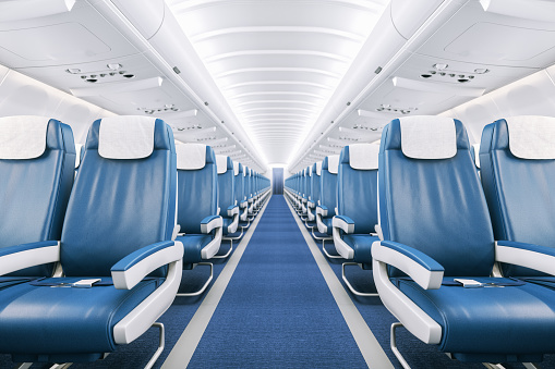 Interior of a commercial airplane cabin with blue leather seats.