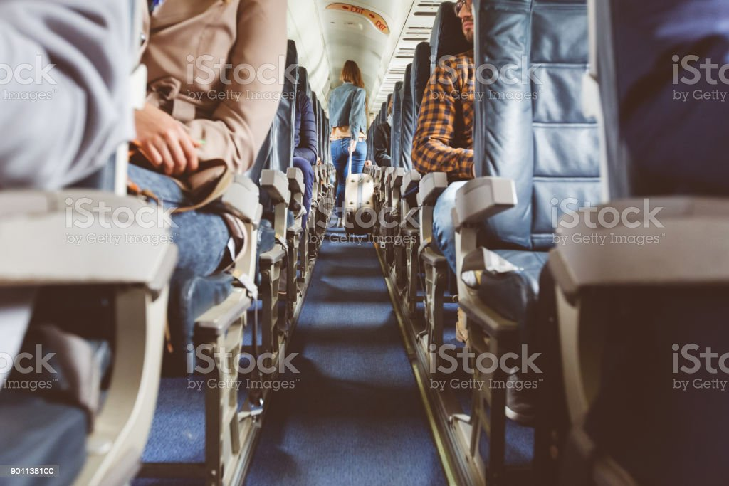Airplane interior with people sitting on seats stock photo