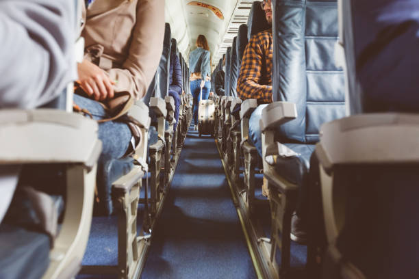 Airplane interior with people sitting on seats Interior of airplane with people sitting on seats. Passengers with suitcase in aisle looking for seat during flight. passenger stock pictures, royalty-free photos & images