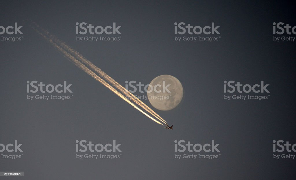 Airplane is crossing the moon stock photo