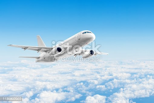 istock Airplane is flying above the day clouds, travel trip vacation. 1135802022