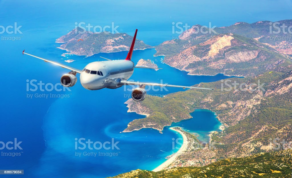Airplane is flying over amazing islands and mediterranean sea at bright day. Landscape with white passenger airplane, mountains and blue water. Passenger aircraft. Business trip. Commercial plane stock photo