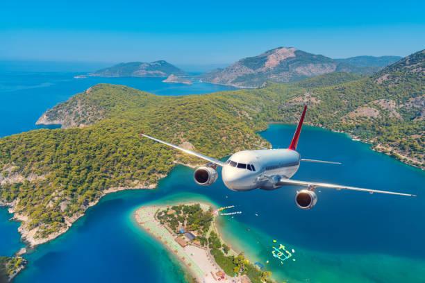 Flugzeug fliegt über erstaunliche Berge mit Wald und Meer bei Sonnenaufgang im Sommer. Landschaft mit weißen Passagier Flugzeug, Himmel, Inseln und blauen Wasser. Passagierflugzeug. Reise- und Resort. Tourismus – Foto