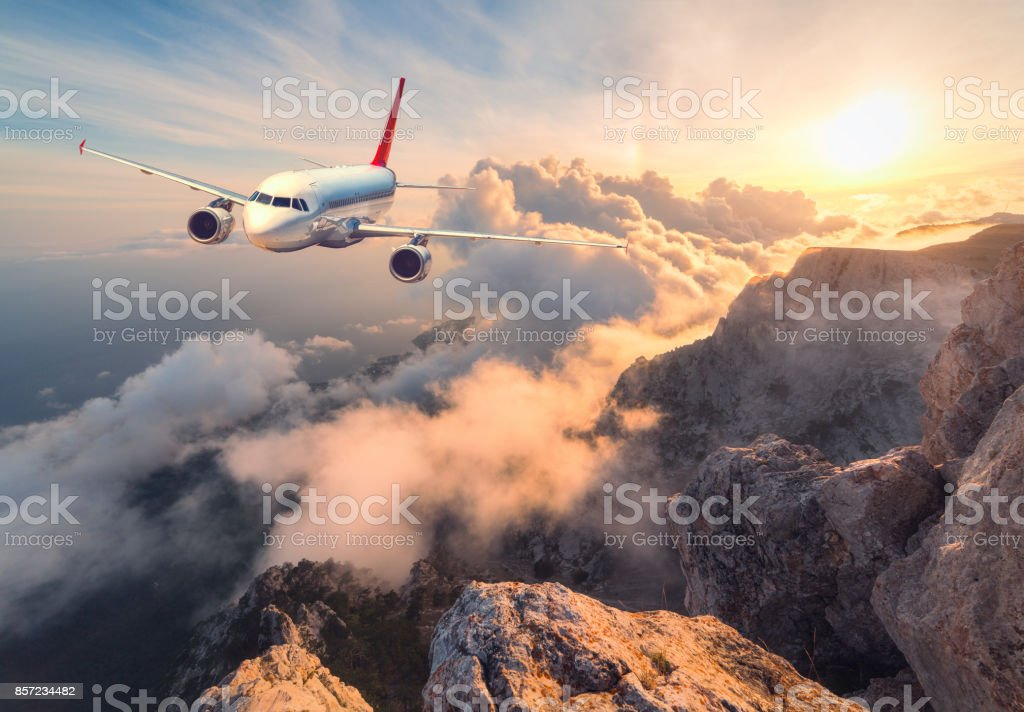 Airplane is flying over clouds at sunset. Landscape with white passenger airplane, mountains, sea and orange sky with sun in summer. Passenger aircraft is landing. Business travel. Commercial plane stock photo