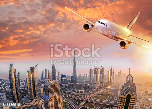istock Airplane is flying over Dubai against colorful sunset in United Arab Emirates 843136516