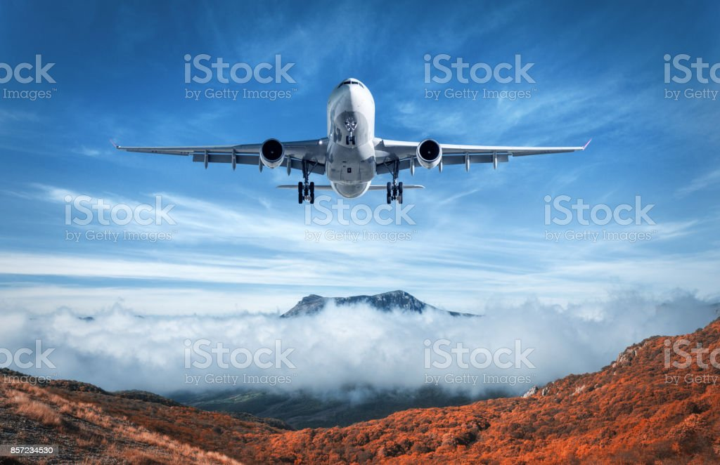 Airplane is flying over low clouds and mountains with autumn forest. Amazing landscape with passenger airplane, trees, mountains, blue cloudy sky. Passenger aircraft. Business travel. Commercial plane stock photo