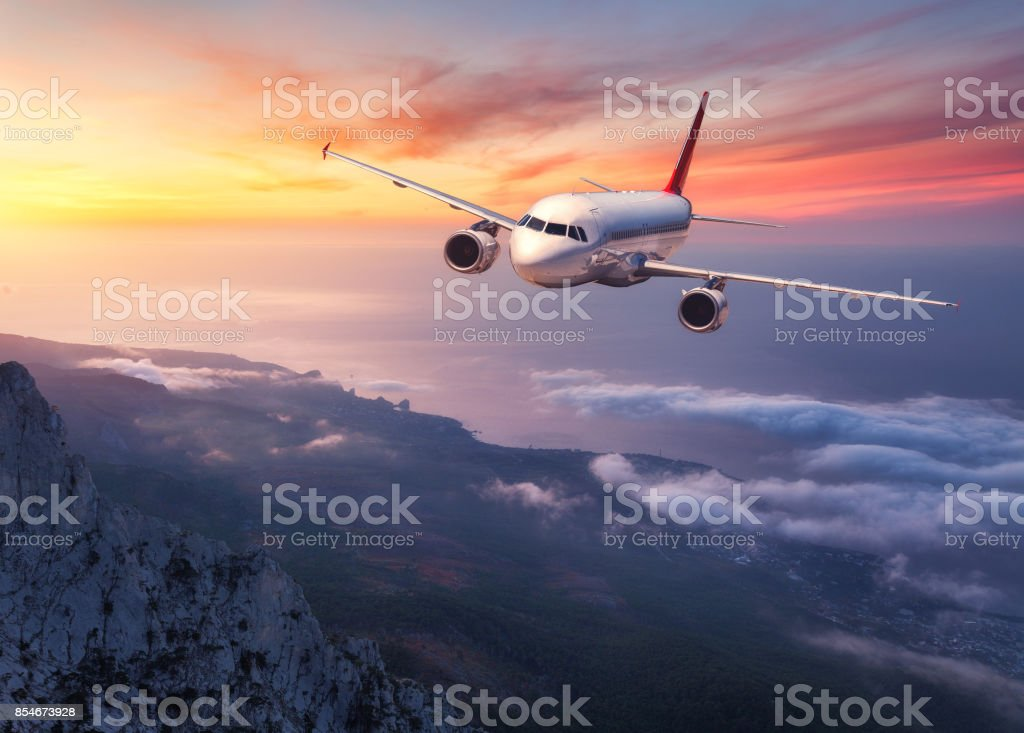 Airplane is flying over low clouds at sunset. Landscape with passenger airplane, mountains, sea and orange sky with red clouds in summer. Passenger aircraft. Business travel in Europe.Commercial plane stock photo