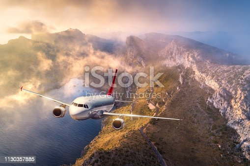 1058205304 istock photo Airplane is flying over mountains and low clouds at sunset in summer. Landscape with passenger airplane, sky in clouds, rocks, sea, sunlight. Business travel. Commercial plane. Aerial view of aircraft 1130357885