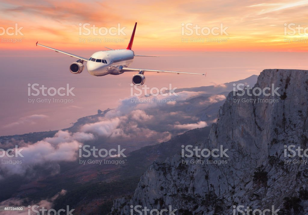 Airplane is flying over rocks and clouds at sunset. Landscape with passenger airplane, mountains, sea and orange cloudy sky in summer. Passenger aircraft. Business travel in Europe. Commercial plane stock photo