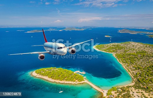 1058205304 istock photo Airplane is flying over small islands and sea at sunny day in summer. Aerial view of passenger airplane, tropical seashore, mountains with green trees, sky and blue water. Top view of aircraft. Travel 1209224873