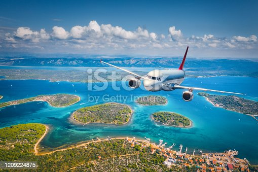 1058205304 istock photo Airplane is flying over small islands and sea at sunny day in summer. Aerial view of passenger airplane, tropical seashore, mountains with green trees, sky and blue water. Top view of aircraft. Travel 1209224875