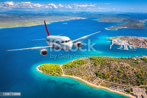 1058205304 istock photo Airplane is flying over small islands and sea at sunset in summer. Aerial view of passenger airplane, tropical seashore, mountains with green trees, sky and blue water. Top view of aircraft. Travel 1206720999