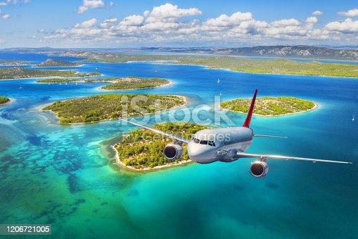 1058205304 istock photo Airplane is flying over small islands and sea at sunset in summer. Aerial view of passenger airplane, tropical seashore, mountains with green trees, sky and blue water. Top view of aircraft. Travel 1206721005