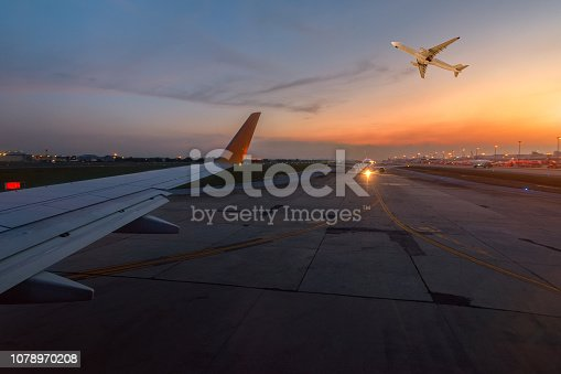 istock Airplane is taxiing to the runway for take off in beautiful sunset. 1078970208