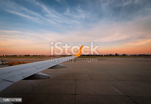 istock Airplane is taxiing to the runway for take off in beautiful sunset. 1080147558