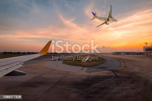 istock Airplane is taxiing to the runway for take off in beautiful sunset. 1085077326