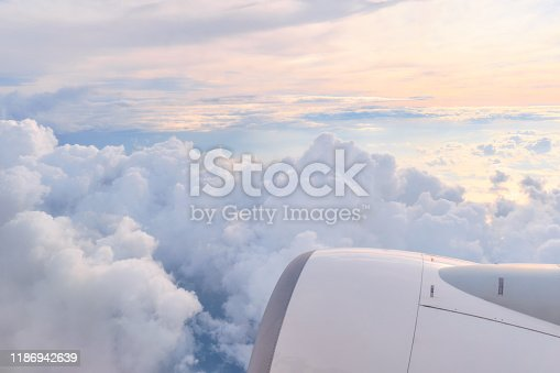 Airplane jet engine in fluffy white clouds with orange and light blue sun light in the horizon.